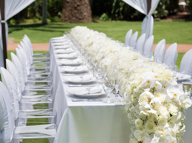A dining table decorated with flowers at an outdoor wedding reception venue